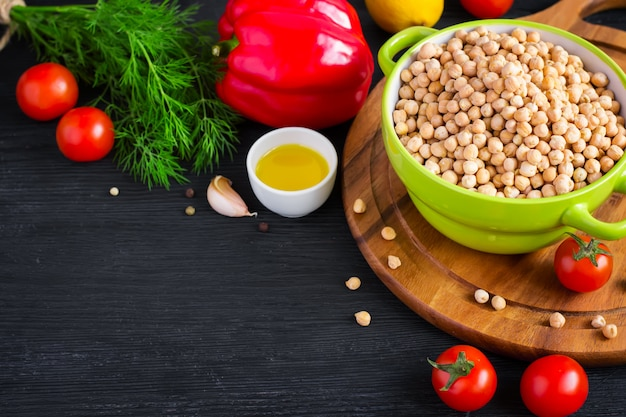 Black background with chickpeas and colorful vegetables