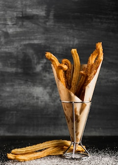 Black background with churros on a wrapping paper
