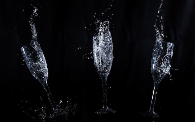 Sfondo nero con bicchieri di cristallo in movimento