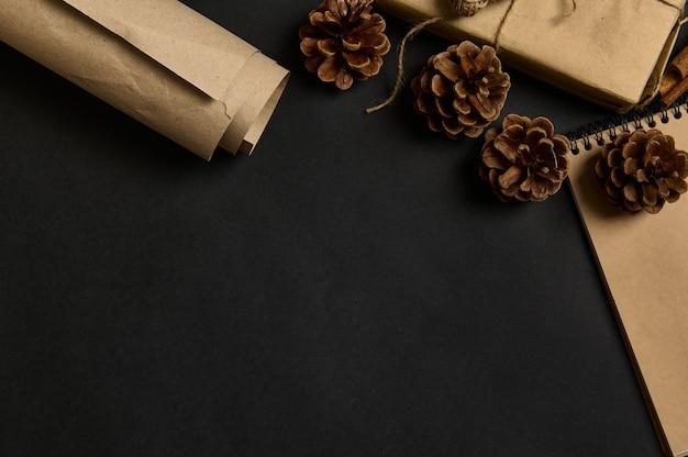 松ぼっくりと黒の背景、画像の隅にクラフト包装紙でトリミングされたクリスマスプレゼント