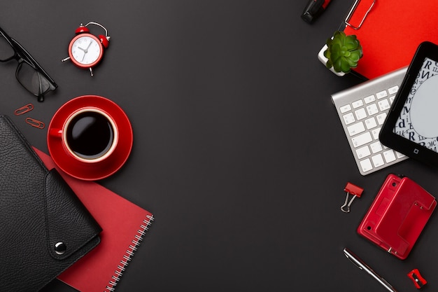 Black background with red coffee cup, notepad, alarm clock  and flowers in top view