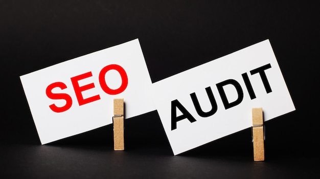 On a black background on wooden clothespins, two white blank cards with the text seo audit