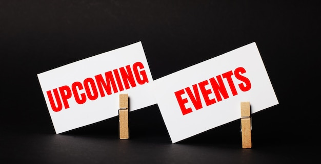 On a black background on wooden clothespins, two white blank cards with the text upcoming events