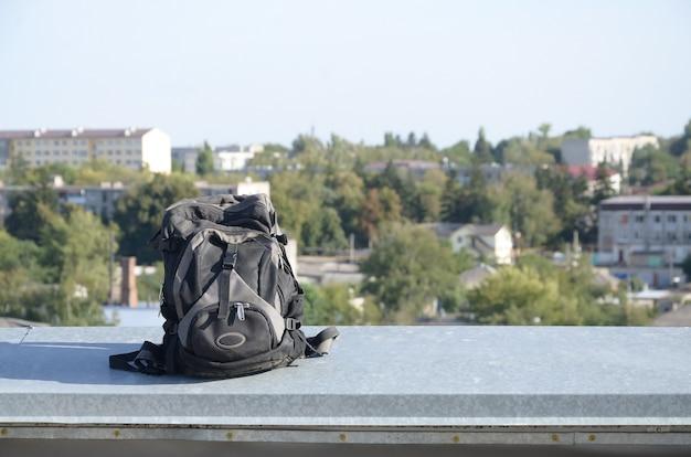 Black backpack lies on metal border of residental multistorey building rooftop in sunny weather outdoors