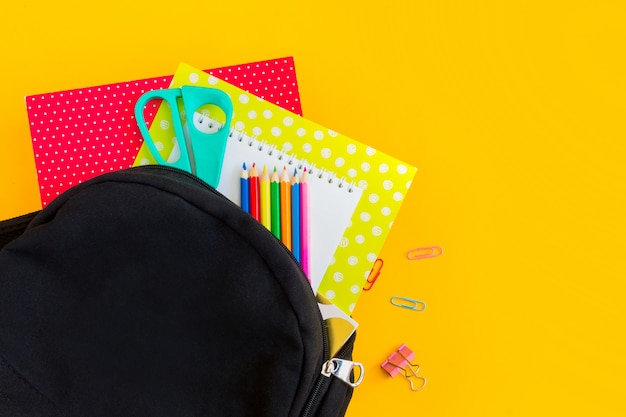 Black backpack and school supplies on a yellow background with copy space, flat lay.