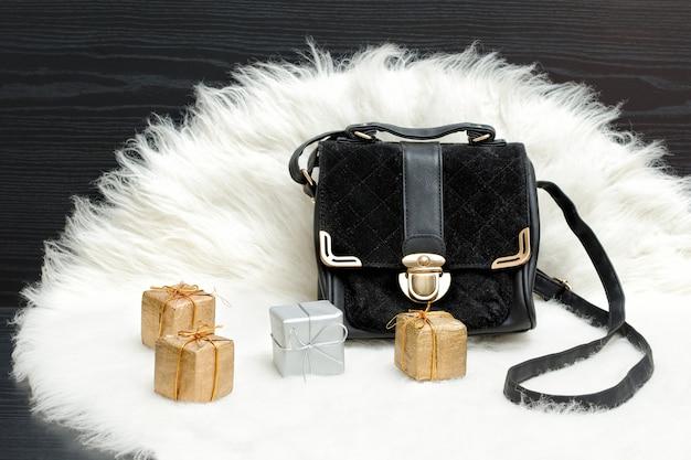 Черная сумка и подарочная коробка на белом меху. модная концепция. праздничный шоппинг