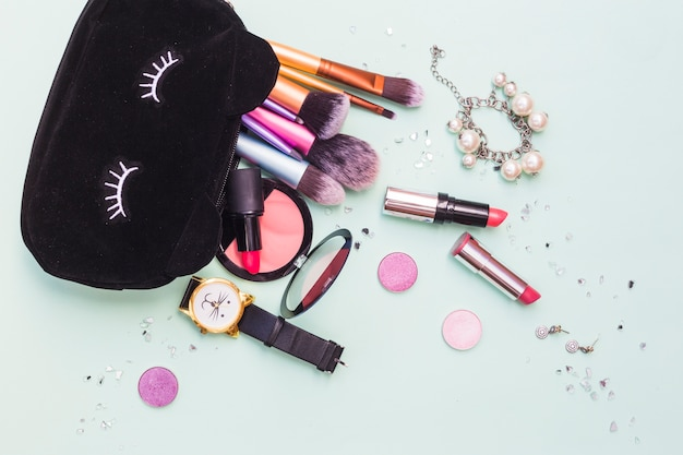 Black bag with makeup brushes; bracelet; wristwatch and cosmetics product on pastel background