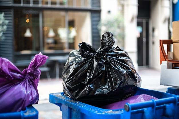 E sacchi neri di immondizia su un bidone della spazzatura durante il giorno