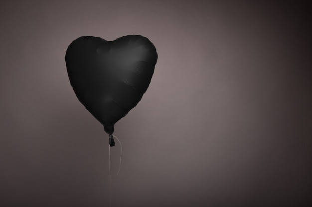 スタジオの灰色の背景にハートの形をした黒いボール