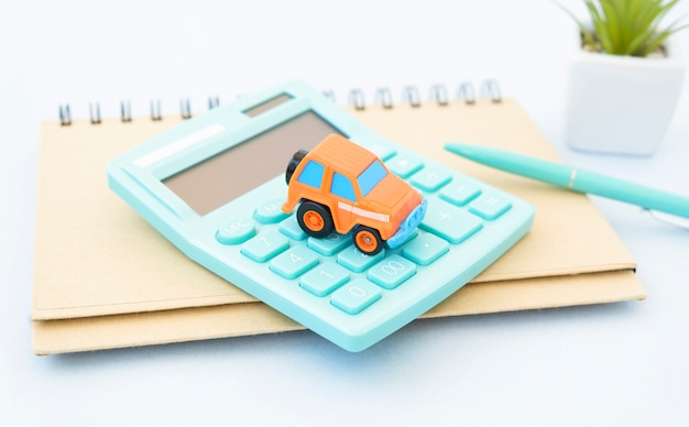 Black ballpoint pen, calculator and red car on paper form, blur with bright background, out of focus