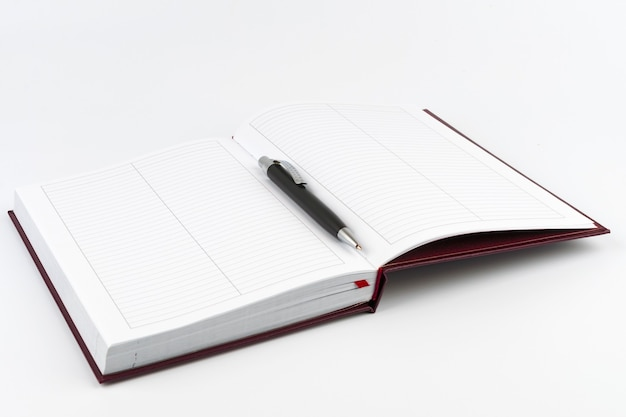Black ballpoint pen in the center of an open diary on white background