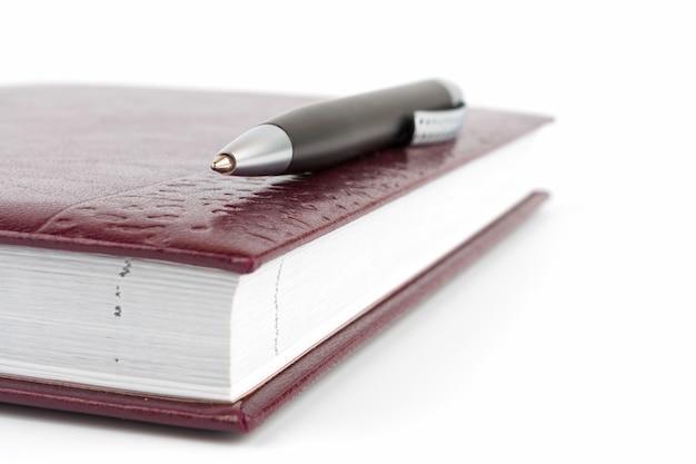 Черная шариковая ручка, лежащая на кожаном переплете дневника