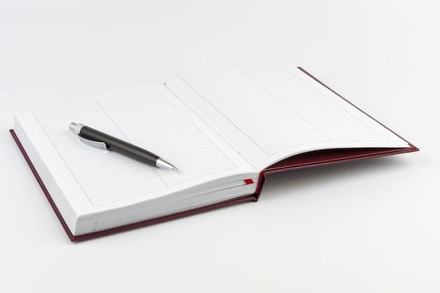 Черная шариковая ручка на открытом дневнике на белом фоне