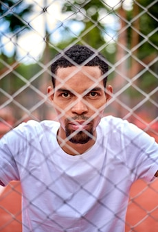 Black basketball player holding the chain link fence with hands