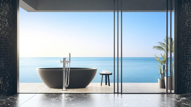 Черная ванна на террасе с деревянным полом у пейзажного бассейна в современном пляжном домике