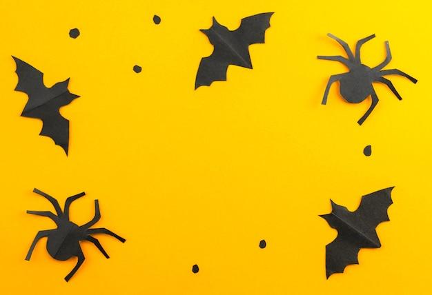 紙で作られた黒いコウモリとクモのシルエット。ハッピーハロウィンのコンセプト。休日のフレーム。