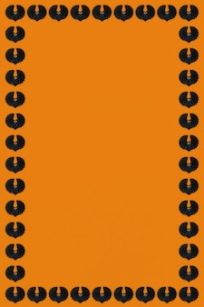 オレンジ色の背景に黒いコウモリハロウィンフレームデザインリソース
