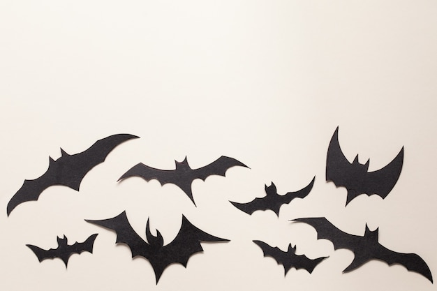黒コウモリ紙カット背景。ハロウィーンの背景。かわいい漫画の不気味なキャラクター。フラットレイ。