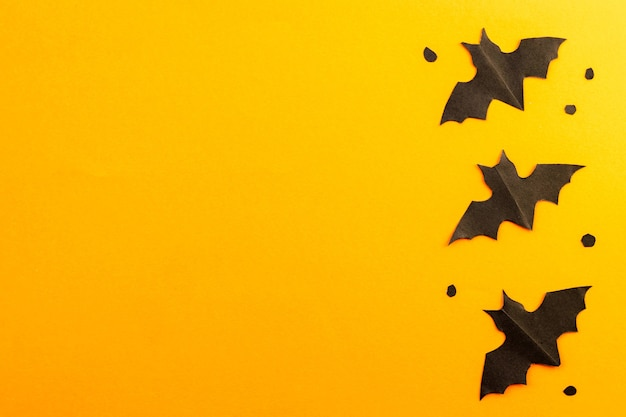 Black bats silhouettes made from paper on orange background. flat lay. happy halloween.