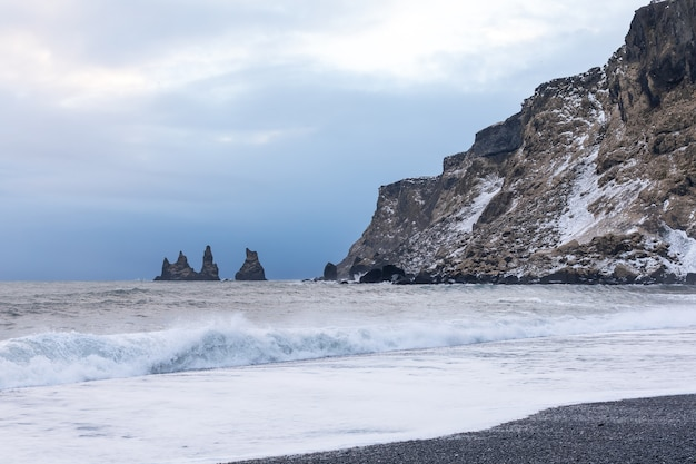 Черный пляж, скалы и волны возле вик во время зимнего заката