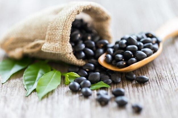 나무로되는 숟가락, 복사 공간에 검은 콩.