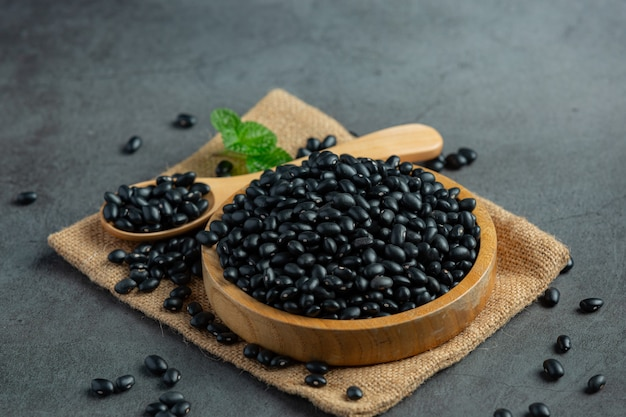 Black bean in small wooden plate place on sack fabric