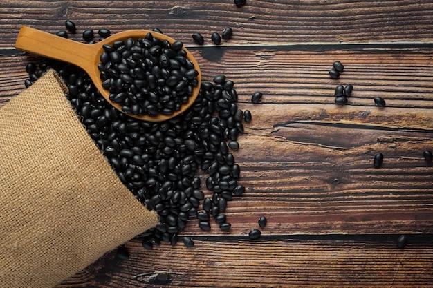 Fagiolo nero in un piccolo cucchiaio di legno posto accanto al sacco pieno di fagioli neri