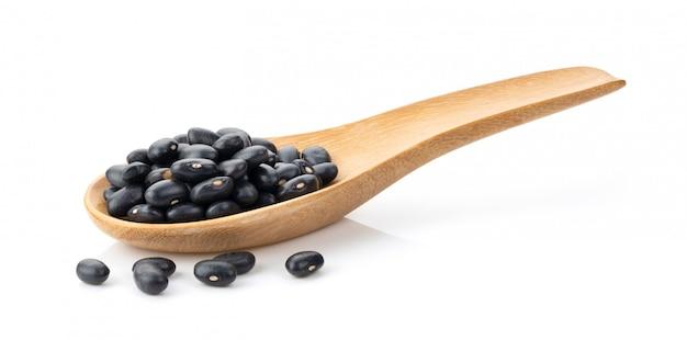 白の完全な被写し界深度に分離された木のスプーンで黒豆