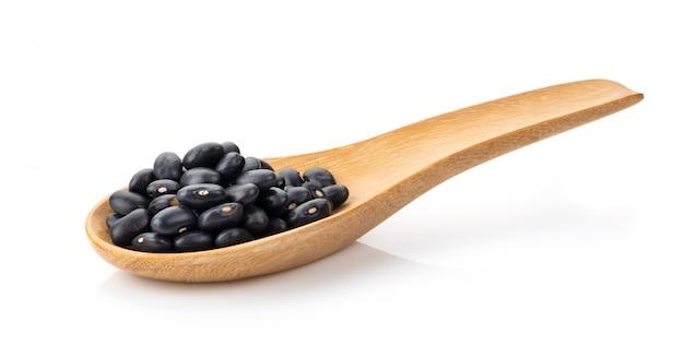 白で隔離される木のスプーンで黒豆