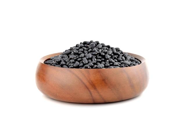 白で隔離される木製のボウルの黒豆