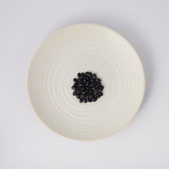 白い背景の上のプレート上の黒豆。上面図。
