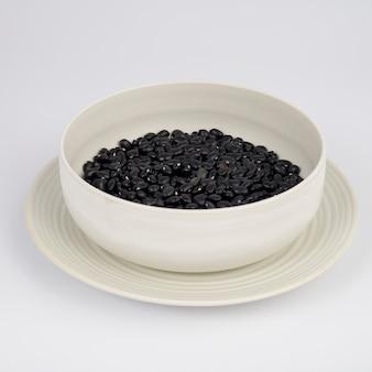 白い背景の上のプレート上の黒豆。