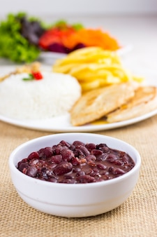 Черная фасоль на белой тарелке на кухонном полотенце из сырого хлопка с полной тарелкой с рисовой курицей и картофелем фри позади