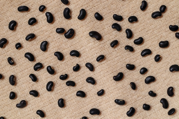 Black beans seeds on cream fabric