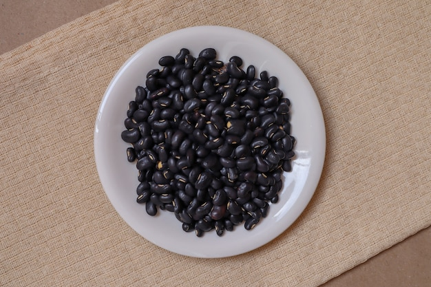 갈색 종이 배경에 크림 색된 식탁보에 흰색 세라믹 컵에 검은 콩 씨앗.
