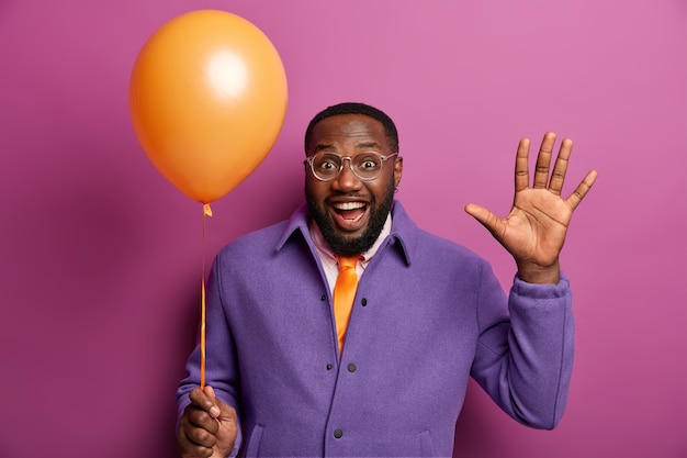 Black bearded man entrepreneur waves palm, comes on corporate party, holds inflated helium balloon, enjoys festive event in business company, wears formal clothes, isolated on purple  wall
