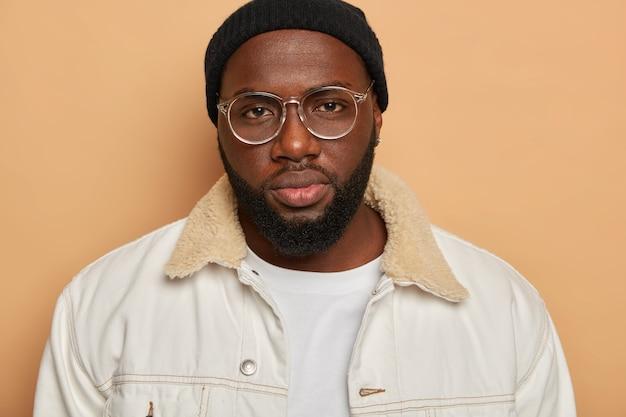 黒ひげを生やした男は非常に深刻な外観をしており、透明な眼鏡、黒い帽子と白いシャツを着て、ベージュの背景の上に隔離されたカメラを直接見ています。人間の表情