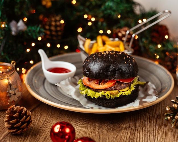 Black beef burger served with french fries ketchup and mayonnaise