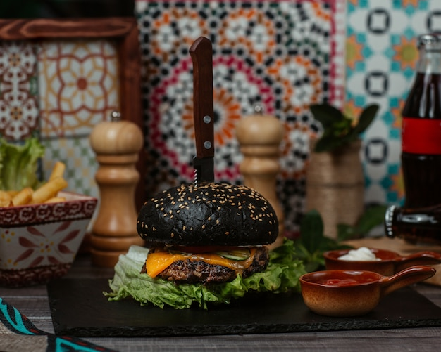 A black beef burger stuffed with vegetables and apetizers and served with cheddar cheese