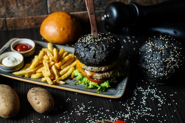 Hamburger di manzo nero con ingredienti e patatine fritte