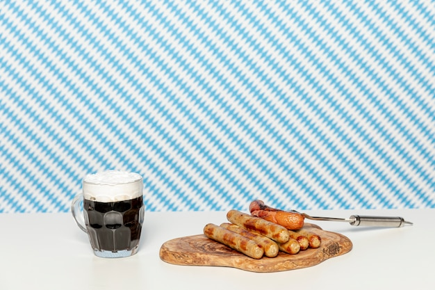 Black beer and german sausages on white table