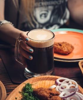 テーブルの上のフライドチキンとマグカップで黒ビール