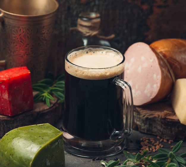 Black beer with green cheese on the table