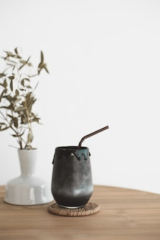 Black beverage drink made from charcoal and milk on vintage style wood table with dry plant leaf decoration pot.