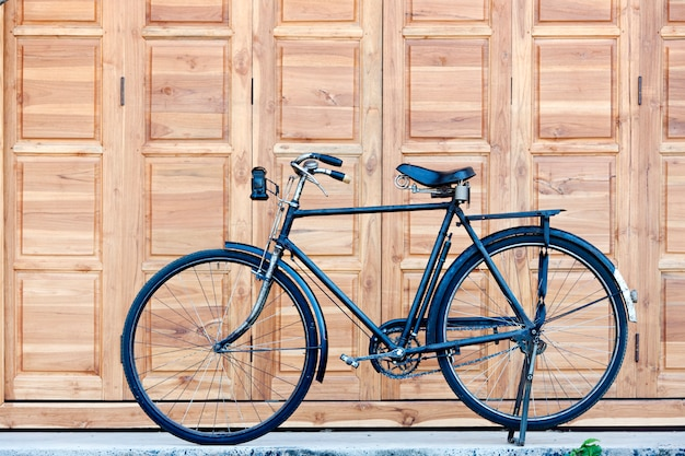 Black bicycle park at footpath .beautiful old style black  bicycle on brown wood door back