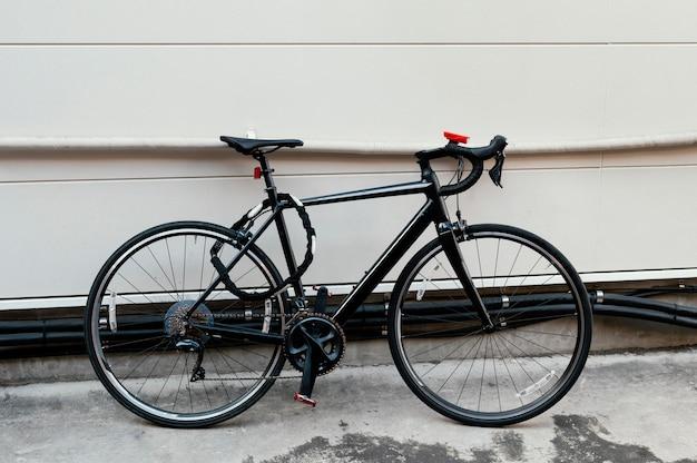 Черный велосипед, привязанный на открытом воздухе