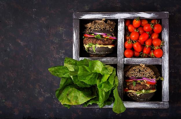 黒の大きなサンドイッチ-ジューシーなビーフバーガー、チーズ、トマト、黒の表面のボックスに赤玉ねぎと黒のハンバーガー。平干し。上面図