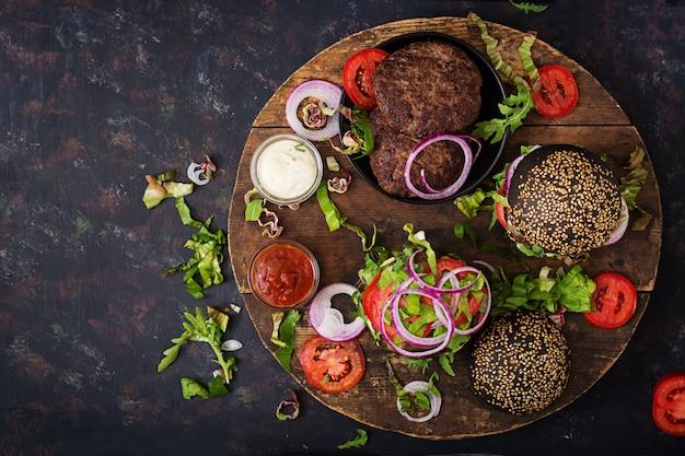Черный большой сэндвич - черный гамбургер с сочным говяжьим гамбургером, сыром, помидорами и красным луком на черной поверхности