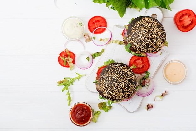 Черный большой сэндвич - черный гамбургер с сочным говяжьим гамбургером, сыром, помидорами и красным луком на светлой поверхности.
