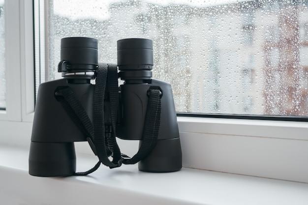 이웃을 관찰하기위한 검은 쌍안경은 유리에 빗방울이있는 창가의 흰색 창틀에 있습니다. 집의 창문에서 환경이나 자연에 대한 매혹적인 관찰